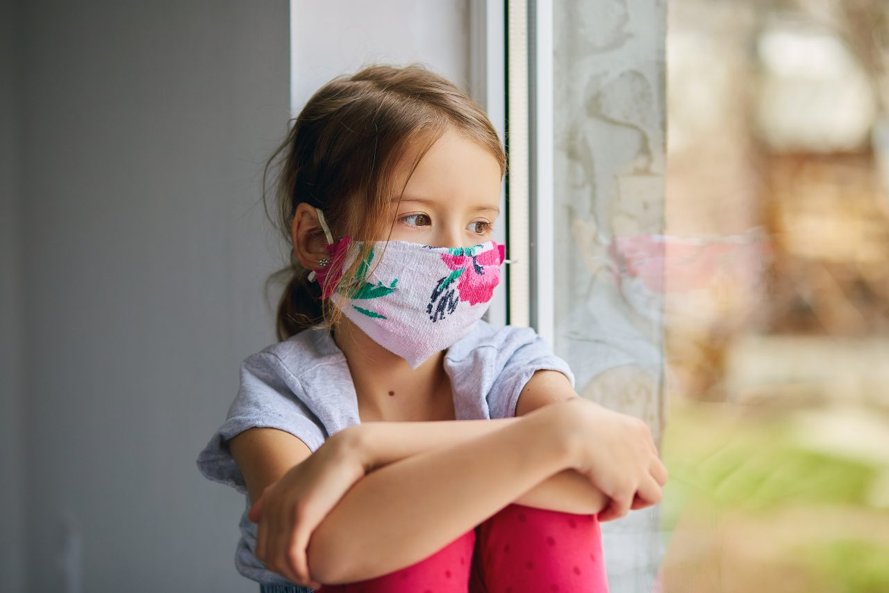 little-girl-child-in-mask-sits-on-windows-coronavi-TDPEMHW-1280x853.jpg